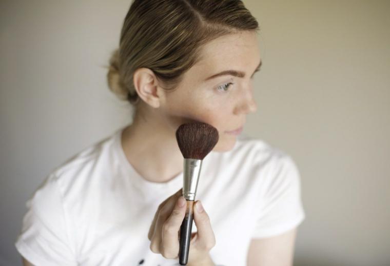 Ragazza che mette il blush con pennello sugli zigomi per un make up di Halloween