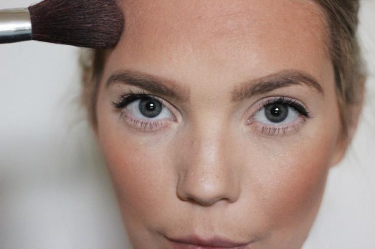 Trucchi per Halloween viso, ragazza che applica la cipria sulla fronte con un pennello