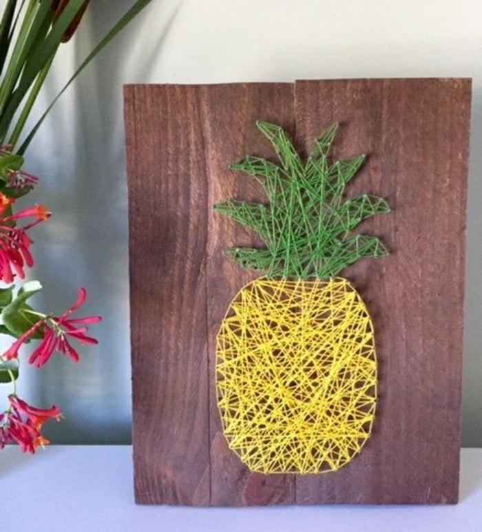 Lavori artigianali fai da te per decorare la casa, pezzo di legno con un ananas di corda gialla e verde