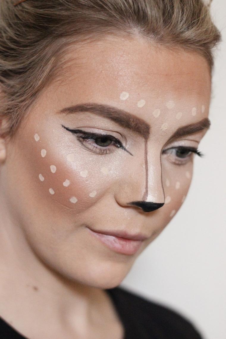 Trucco Halloween ragazza travestita come un cervo, viso con puntini bianchi di correttore e naso nero
