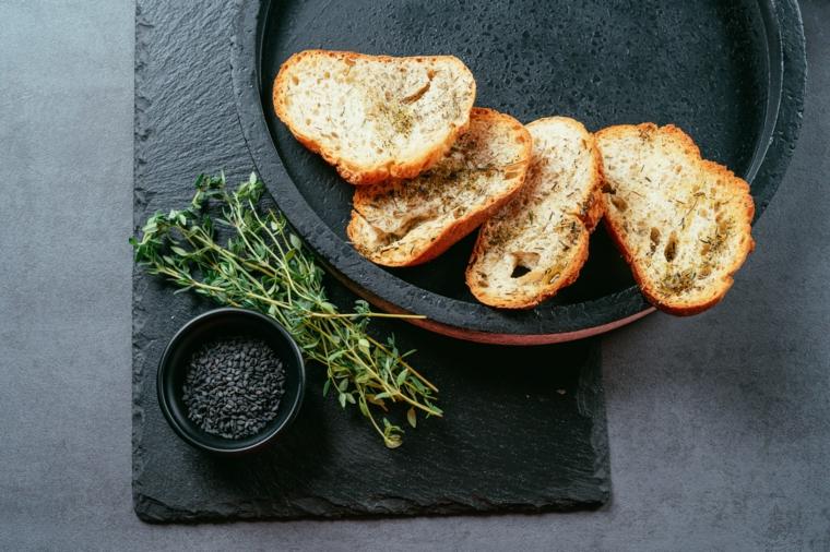 Crostini di pane con rimo e sesamo, hummus di ceci, piatto con fettine di pane all'olio