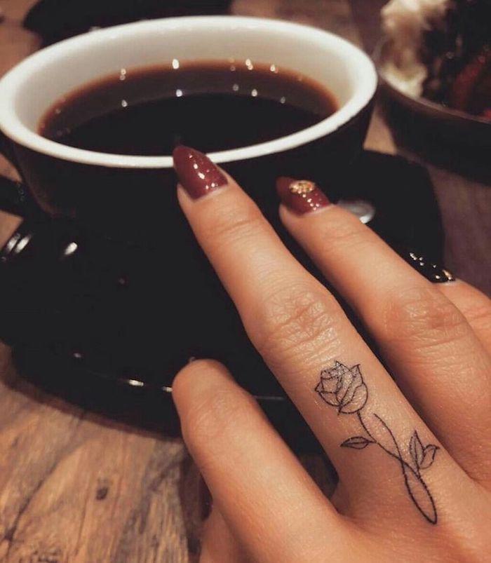 Tatuaggi piccoli sulle mani e un'idea con tattoo rosa sul dito di una donna