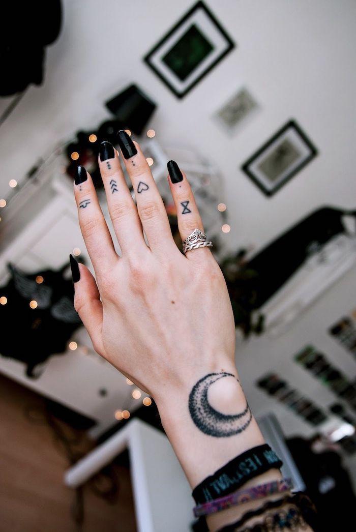 Tatuaggio sul dito di una donna con tanti simboli di frecce e cuori