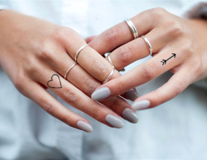 Lettere tattoo, un'idea con due tatuaggi cuore e freccia sulle dita delle mani di una donna