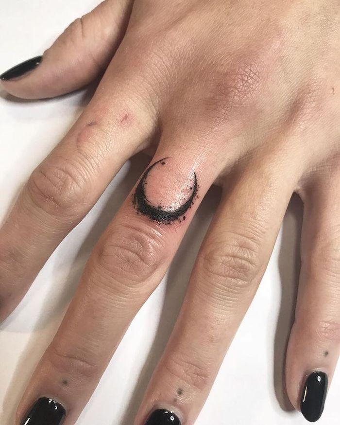 Tatuaggi sulle dita e un'idea con tattoo di luna sul dito medio di una donna