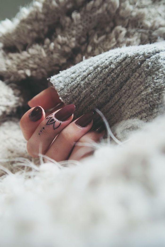 Lettere tattoo, donna con un piccolo tautaggio di fiore di loto sul dito medio