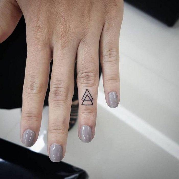 Tatuaggi piccoli mani, idea per un tattoo sul dito anulare con due triangoli