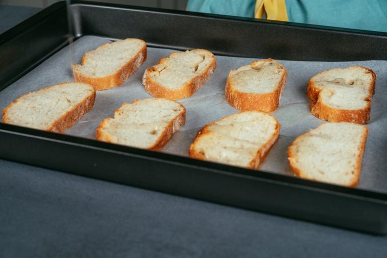 Fette di pane con filo di olio in teglia, ricetta hummus, crostini di pane in una teglia da forno