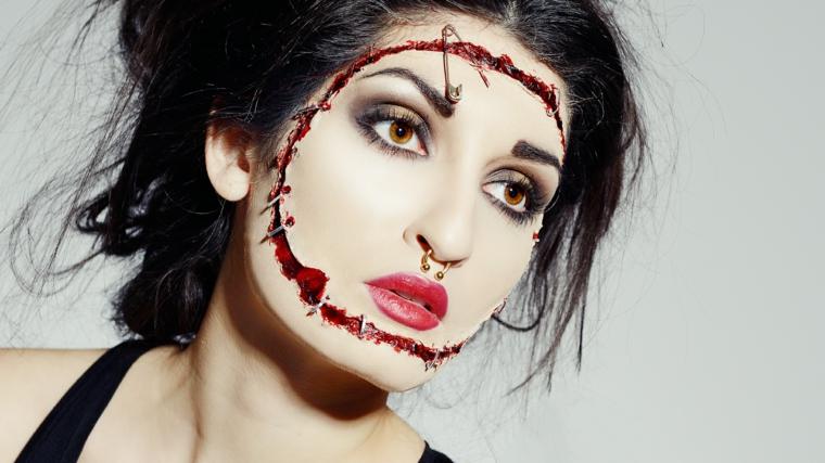 Trucco bambola assassina, ragazza con un viso bianco e tagli con sangue