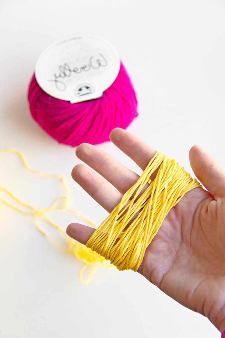 Come fare i pom pom sulla mano con del filo di lana di colore giallo e fucsia