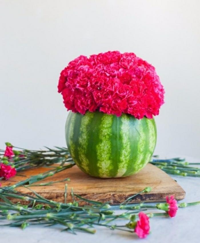 Idee lavoro fai da te con un cocomero intagliato e privato della polpa da essere utilizzato come vaso per fiori