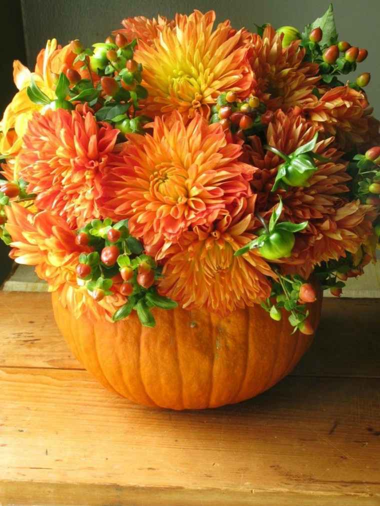 Un centrotavola con un vaso di zucca intagliata e fiori freschi di stagione