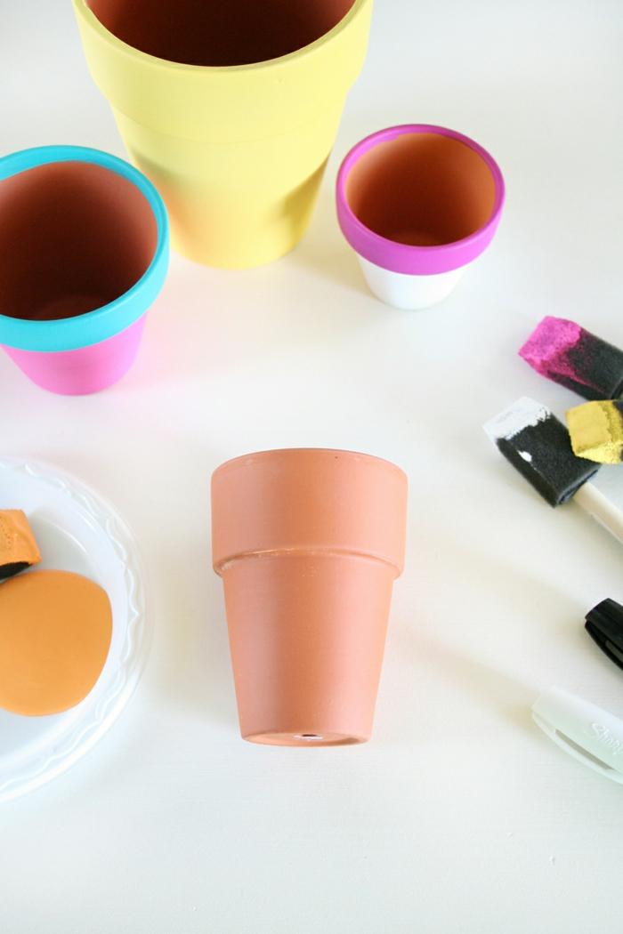 Lavori artigianali con dei vasi di terracotta e pennelli di spugna con della vernice colorata
