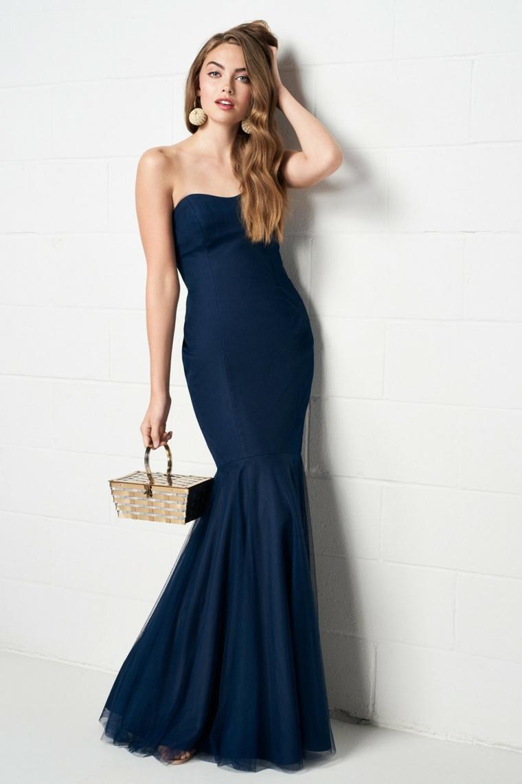 Donna vestita con un abito lungo ed elegante, vestito di colore blu con scollatura a cuore e parte bassa a ruota