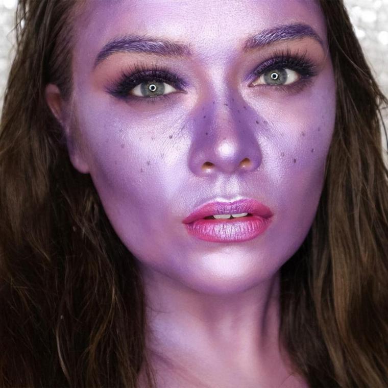 Trucco strega Halloween, ragazza truccata sul viso di colore viola e puntini neri