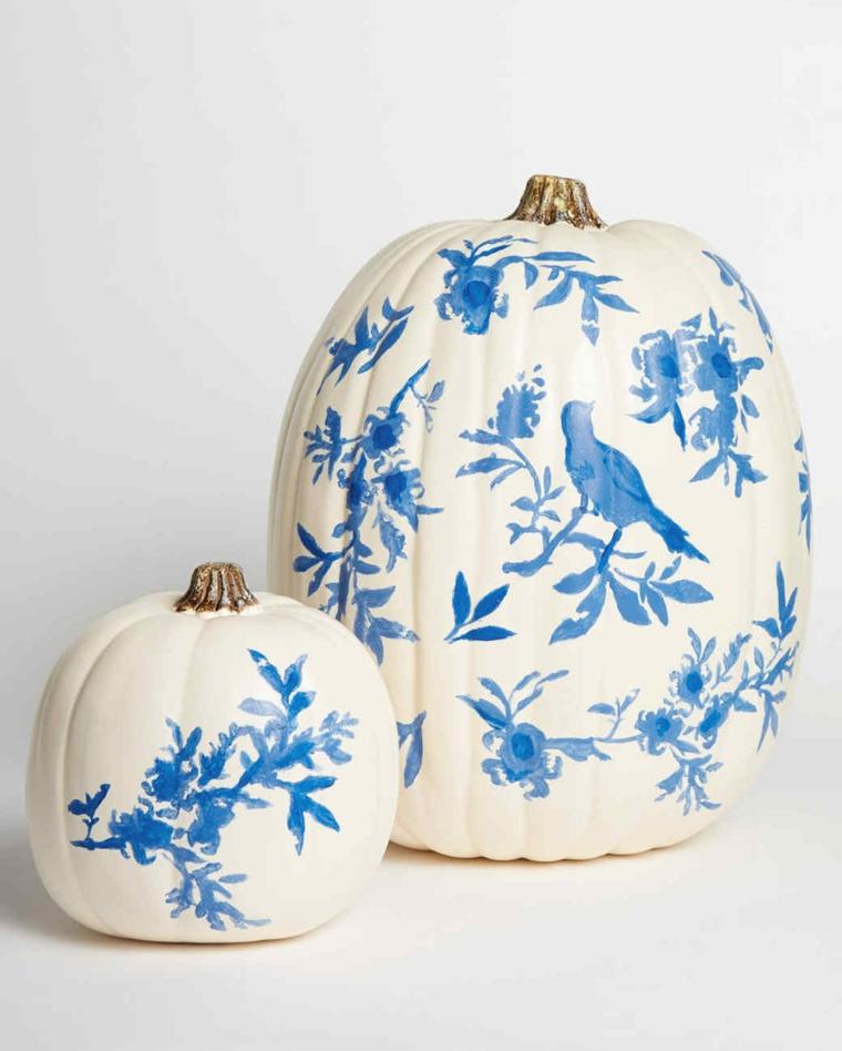 Intagliare zucca di Halloween, una zucca grande di colore bianco con il disegno di un uccellino blu