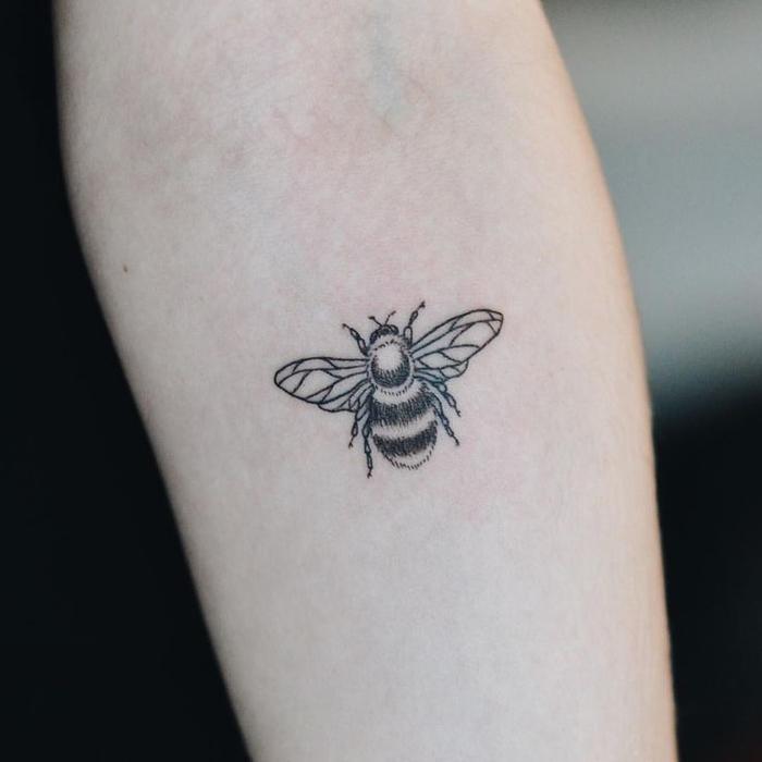 Un piccolo tatuaggio di un'ape con ali dalle forme geometriche