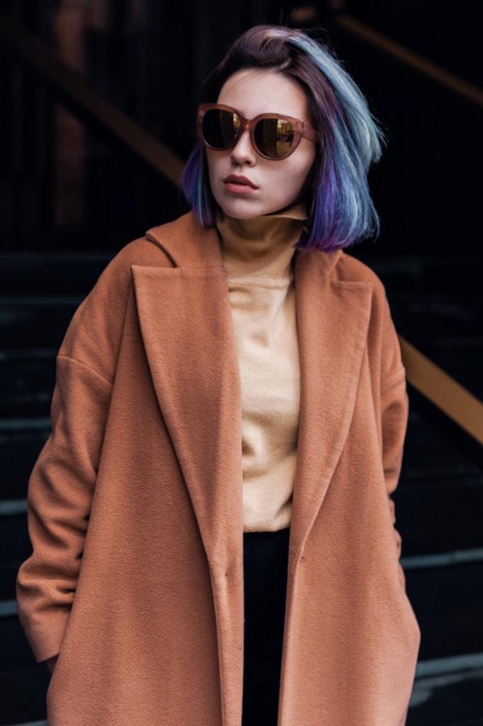 Capelli caschetto di colore viola, ragazza con occhiali da sole e un cappotto marrone