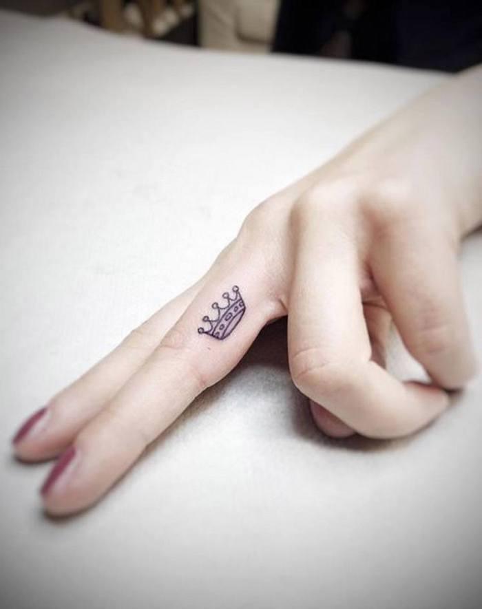 Tatuaggi piccoli mani e un'idea con una corona sul dito medio di una donna