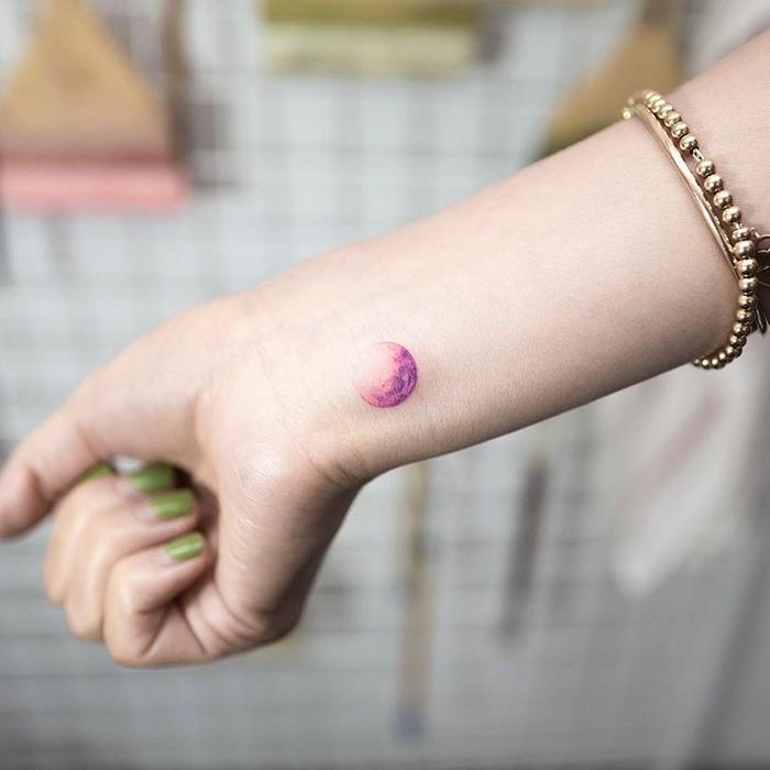 Tattoo femminili e il disegno di una luna piena sul polso della mano di una donna