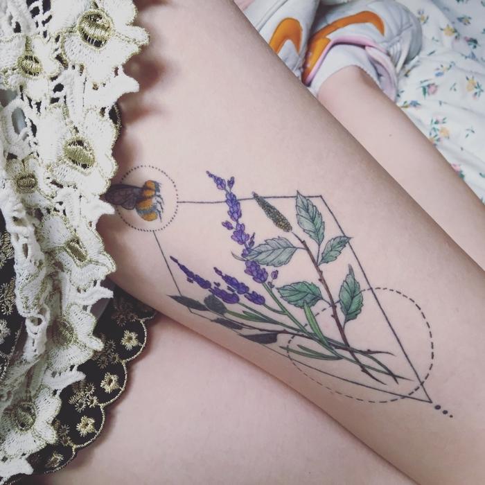 Simbologia tatuaggi e un disegno colorato di lavanda dentro forme geometriche sulla coscia di una ragazza