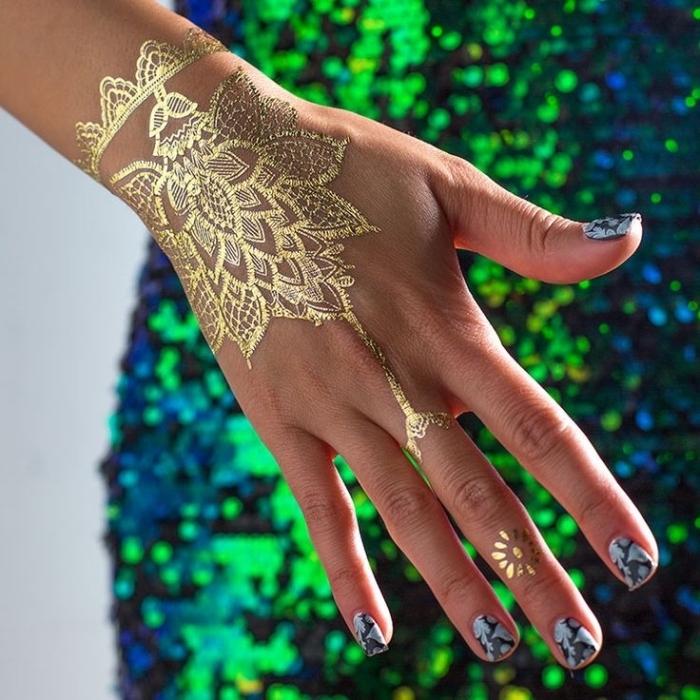 Tatuaggio sul dito e un'idea con Henna tatto in oro sulla mano di una donna