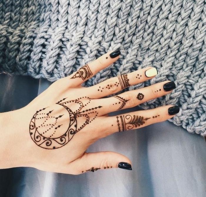 Tatuaggi sulle mani e un'idea con un tattoo Henna di una donna con smalto bianco e nero