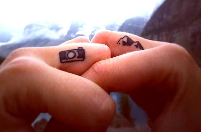 Idea per delle mani tatuate, tattoo di coppia con macchina fotografica e montagne