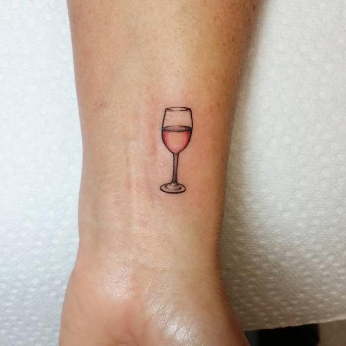 Il polso della mano di una donna tatuato con un bicchiere di vino