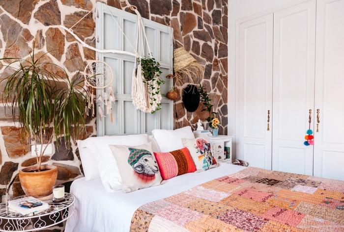 Camera da letto decorata con merletti e pizzi, parete con pietre a vista e armadio a muro