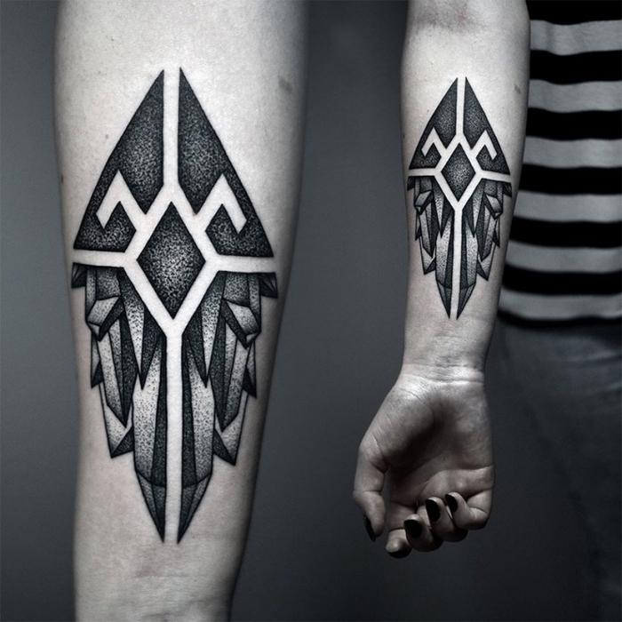 Un tatto maschile sul braccio con il disegno di tante forme geometriche