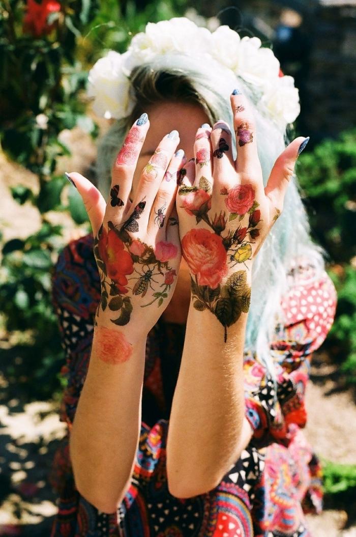 Tatuaggi sulle dita di una ragazza con fiori e farfalle colorate