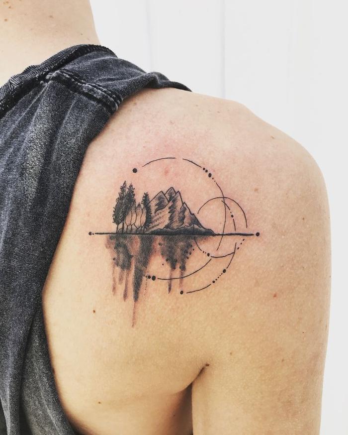 Tatuaggio geometrico sulla spalla di un uomo con raffigurato una foresta riflessa nell'acqua