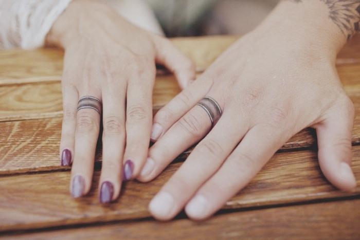 Tatuaggio sulle dita di un uomo e una donna con gli anelli da fidanzamento