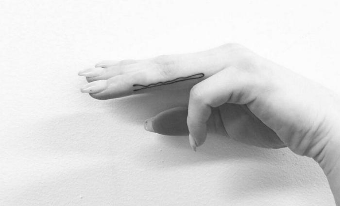 Il dito anulare di una donna tatuato con il disegno di una forcina