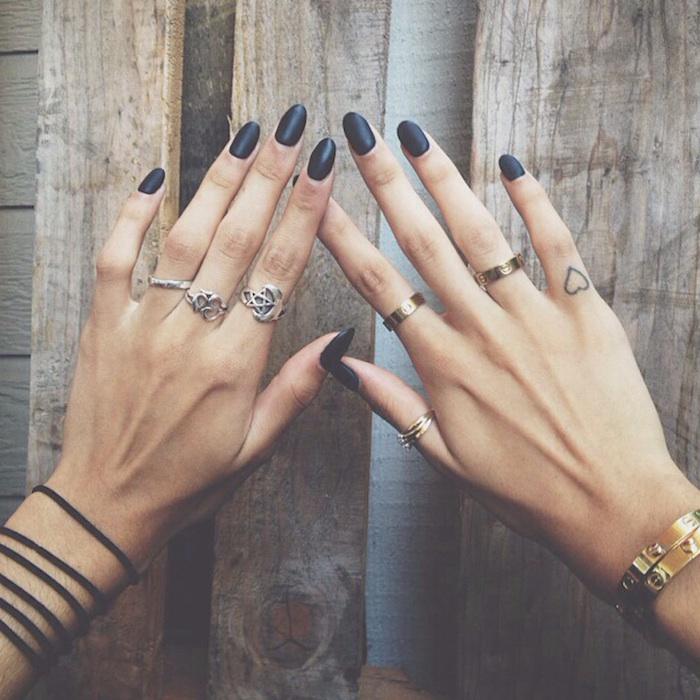 Tattoo sulle mani e un'idea con con cuore piccolo sul dito mignolo di una donna