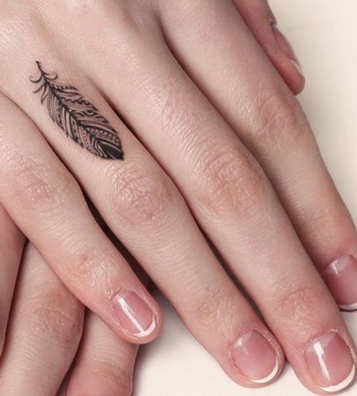 Tattoo sulle mani e un'idea per tatuaggio piuma sul dito anulare di una donna