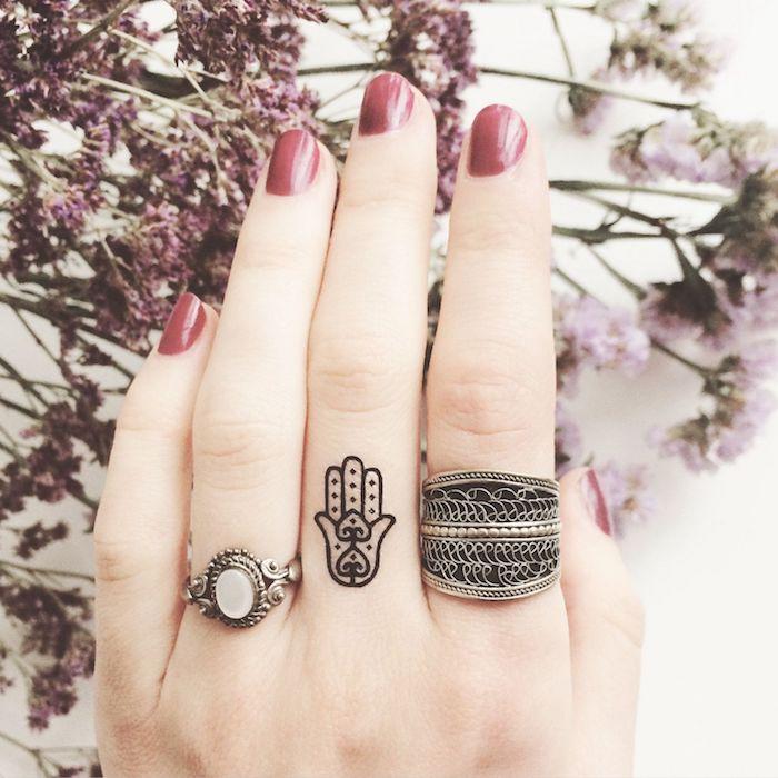 Tatuaggi piccoli mani e un'idea con la mano di fatima disegnata sul dito medio di una donna