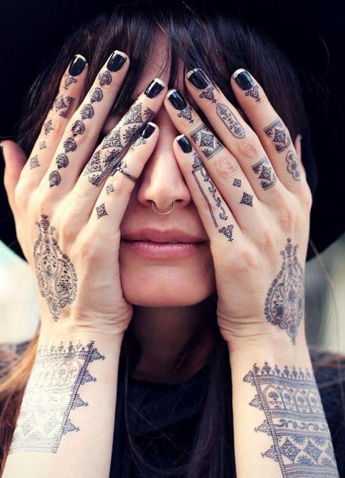 Le mani tatuate di una donna con simboli e disegni mandala