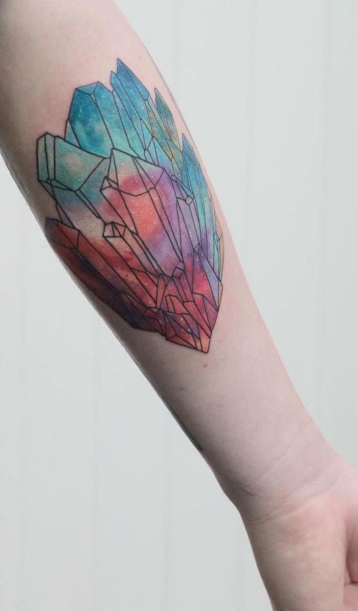 Tatuaggio geometrico colorato sul braccio di un uomo con diverse forme