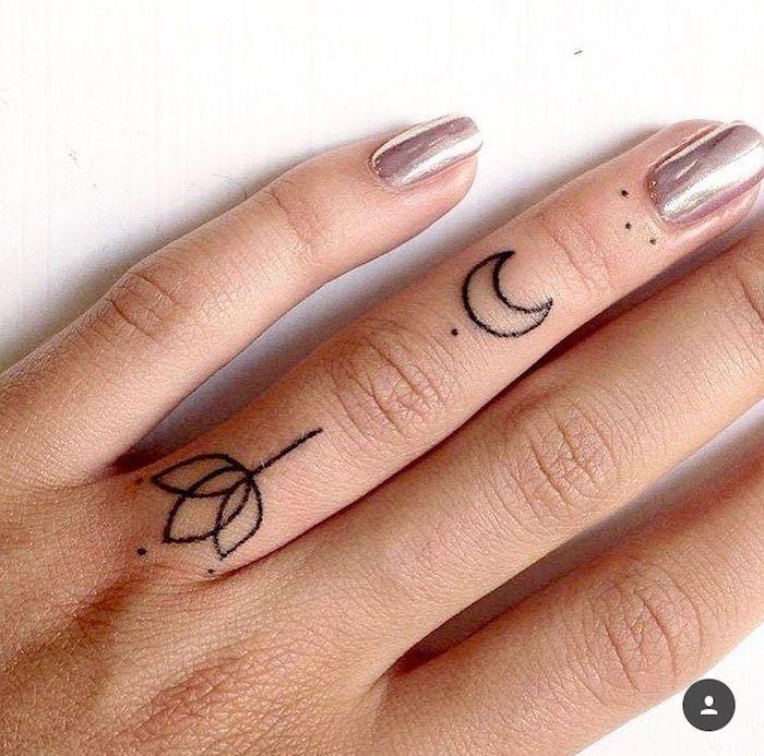 Il dito anulare con due tattto simbolici, tatuaggio fiore di loto e luna