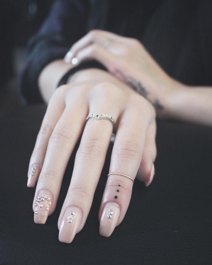 Tatuaggi piccoli sulle mani e un'idea con tre puntini sull'indice di una donna