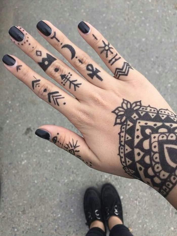 Tatuaggi sulle mani di una ragazza con tanti simboli e disegno mandala sul polso