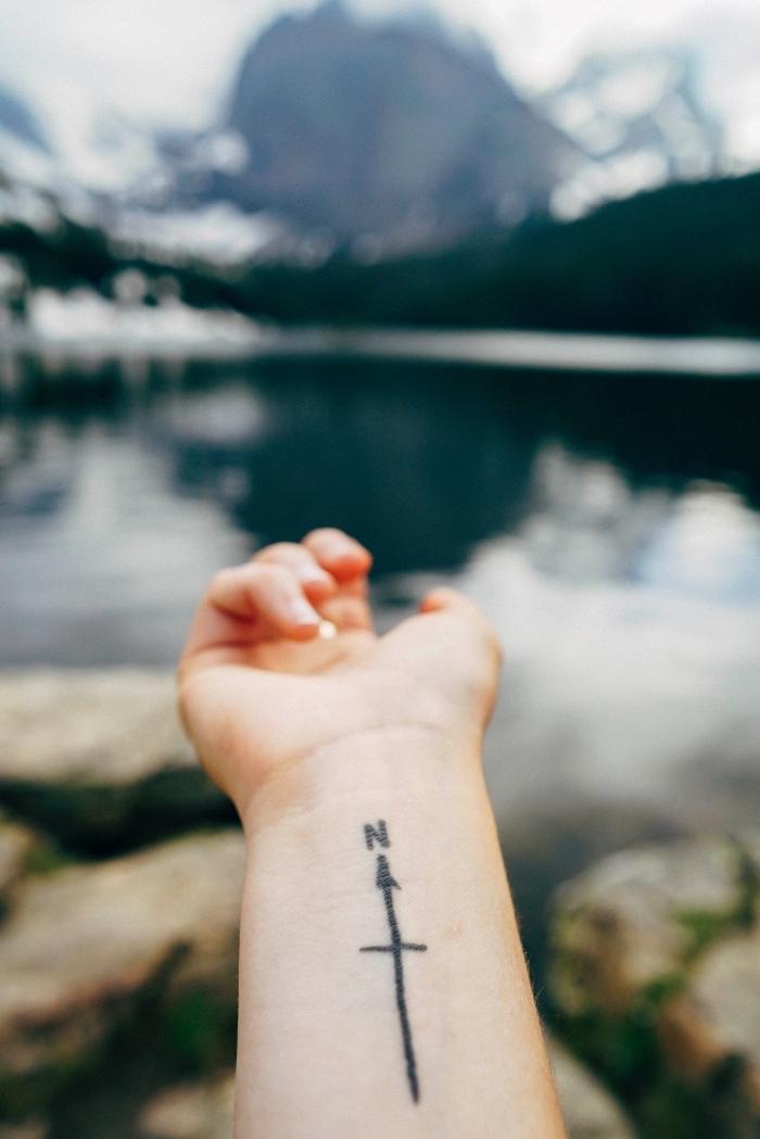 Il polso della mano di una donna tatuato con la direzione nord e una freccia
