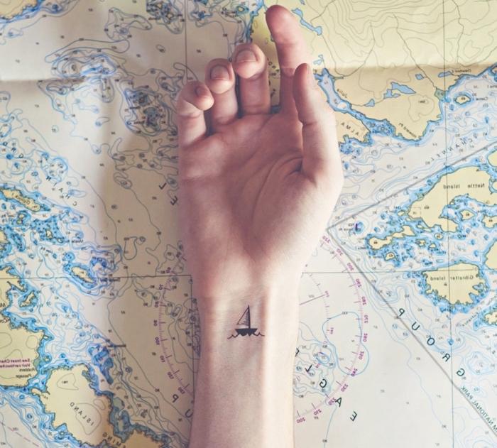 Idea tatuaggi piccoli femminili, tattoo barca a velo sul polso della mano di una donna