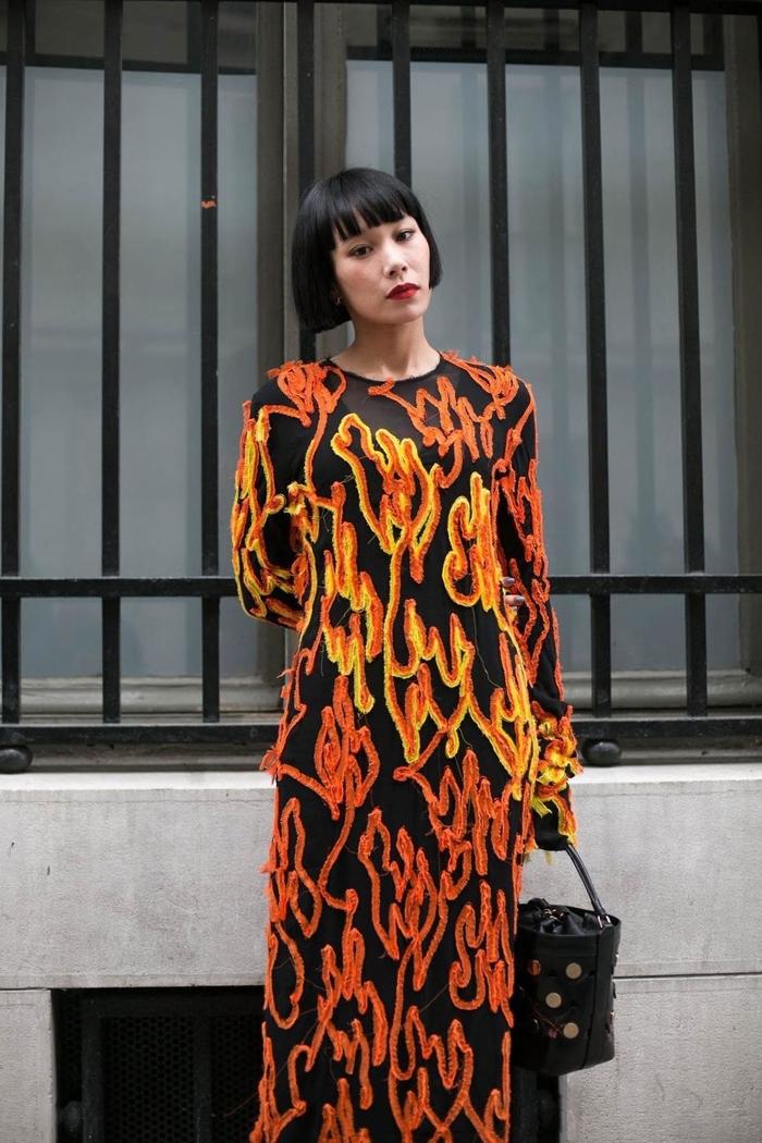 Idea per un taglio ci capelli a caschetto con frangia, abito lungo nero con decorazioni di colore arancione