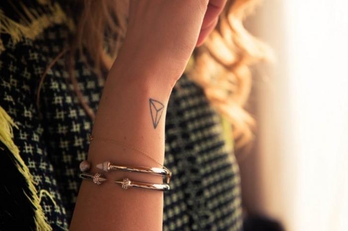 Tatuaggi simboli e un piccolo tattoo con forma geometrica sul polso della mano di una donna