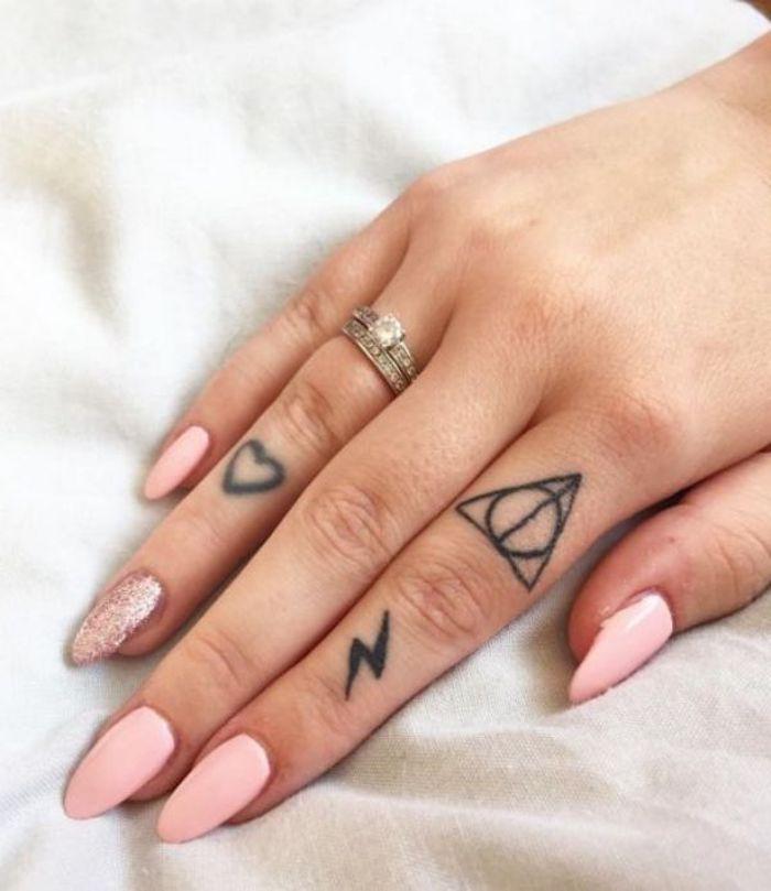 Tatuaggi simbolici sulle dita della mano di una donna con smalto rosa