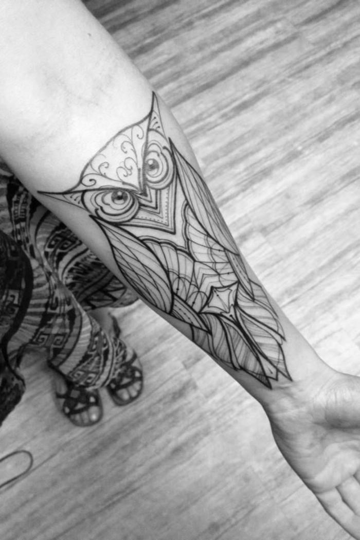 Geometric tattoo e un disegno di gufo sull'avambraccio di una ragazza