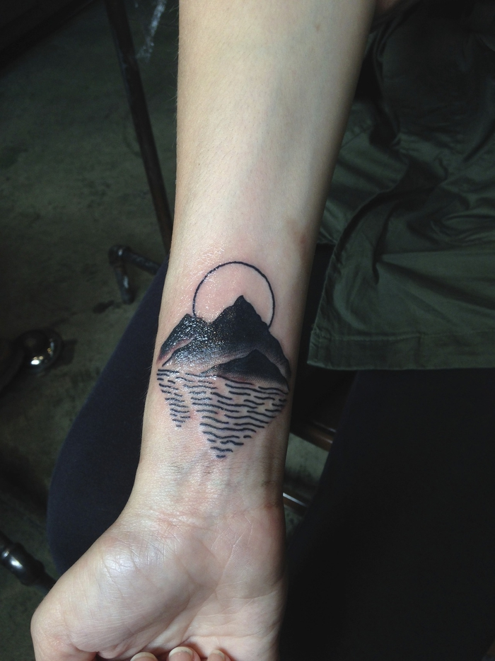 Simboli geometrici e un'idea per tatuaggio sul polso di una montagna che si riflette sul mare